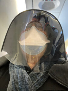 Jed wearing mask and face shield and hood, on plane.
