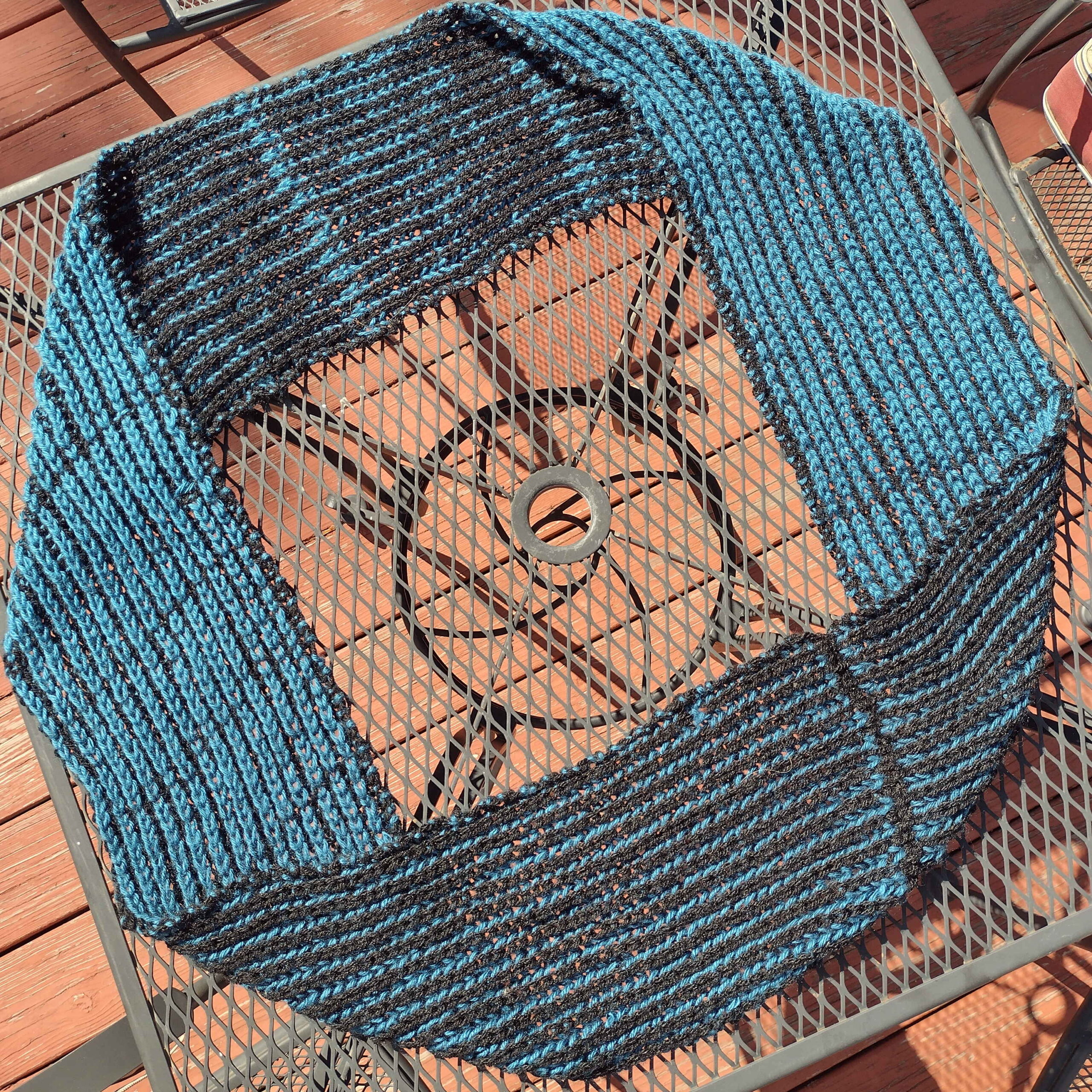 Picture of a turqoise-and-black ribbed scarf arranged in a loop on a wire-topped patio table