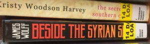 Two book spines, with the end of the titles obscured by stickers. The top one is by Kristy Woodson Harvey and reads 'the secre- southern c-'. The bottom is by James Wolff and reads 'Beside the Syrian S-'.