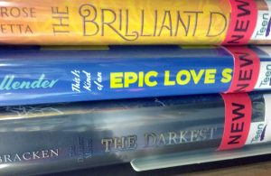 Three book spines, with the end of the titles obscured by stickers. The top one reads 'The Brilliant D-'. The middle one reads 'This is kind of an Epic Love S-'. The bottom one reads 'The Darkest Minds: The Darkest -'.