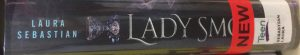 A book spine, with the end of the title obscured by stickers. The author is Laura Sebastian, and the spine reads 'Lady Sm-'